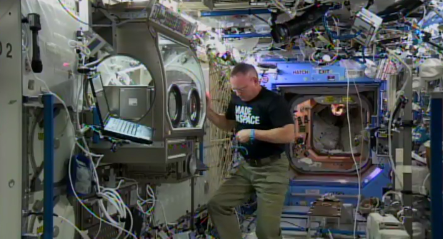 "ISS Commander Barry ""Butch"" Wilmore installs the 3D printer in the Microgravity Science Glovebox."