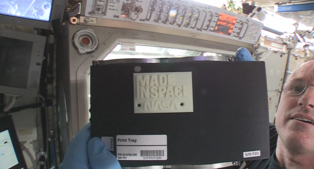 "ISS Commander Barry ""Butch"" Wilmore holds up the first 3-D printed part made in space."