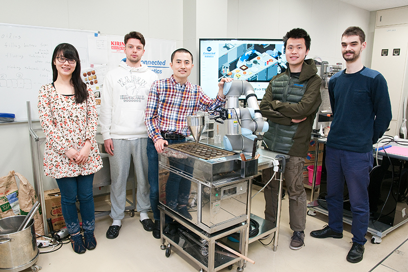 タコ焼きロボットを囲むコネクテッドロボティクスのメンバー、中央が沢登さん